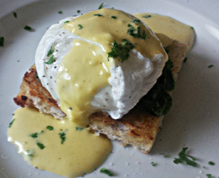 Poached egg on toast with spinach and Hollandaise sauce.